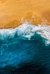 Clean sandy beach with yellow sand and blue sea, vertical photo. Aerial photography of a clean sandy beach. Beautiful beach with yellow sand. Aerial photography of the seascape. Copy space