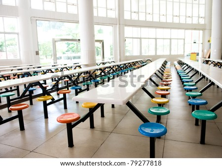 Clean school cafeteria with many empty seats and tables.