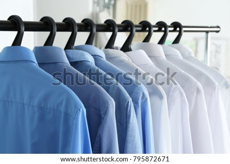 Clean shirts hanging on rack in laundry, closeup #795872671