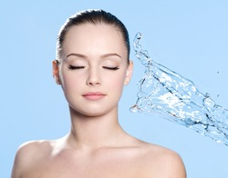 Clean skin on the face of young beautiful young woman and stream of water - blue background