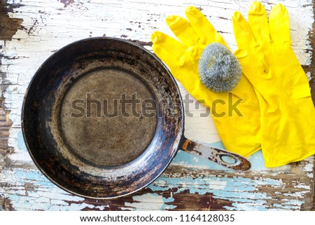 Clean the dirty frying pan with a metal washcloth #1164128035