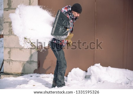 Clean the snow with a shovel. The man shovels snow shovels. Snow shovel in hand. Cleaning the area in the winter. Snow shovel