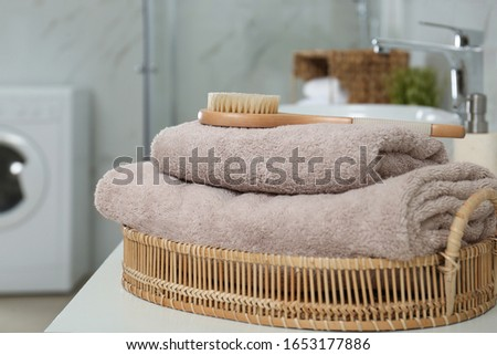 Clean towels and shower brush on countertop in bathroom