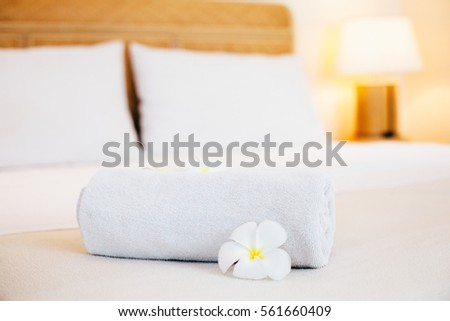 Clean towels on bed in hotel with flowers, white bedding, welcome resort decor.