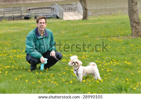 Clean Up After Your Pet - A man and a dog in the park.  The man is holding a plastic poop bag for pet litter control.