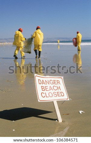 Clean-up crew on beach and warning signage - stock photo
