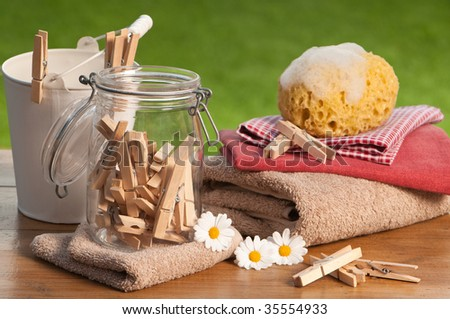 Clean washing with clothes pegs and sponge outdoors on rustic table