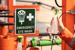 Clean water bottle at emergency eye wash station, using in case of accident to washing personal's eyes when toxic chemical was spilled into eyes. First aid kit for industrial working object photo.