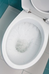 clean water flowing into a white toilet