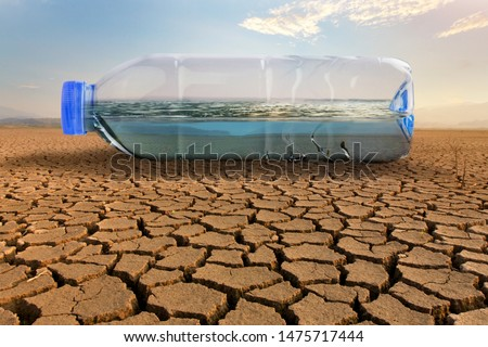 Clean water in plastic bottle on dry land of crakced earth metaphor save water, water crisis and Climate change impact to demand of water