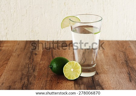 Clean water is standing on a wooden table. Next to a glass of water is lime. Clean water is standing on a wooden table. Next to a glass of water is lime. Healthy lifestyle concept