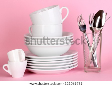 Clean white dishes on pink background