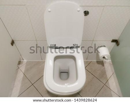 Clean white porcelain public toilet. Public washroom.
