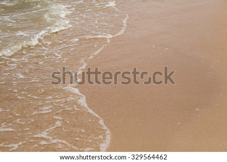 Clean white sand and shallow water with small waves coming for background. #329564462