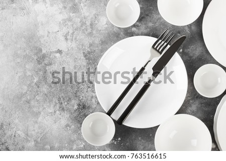 Clean white tableware on a gray background. Top view, copy space #763516615
