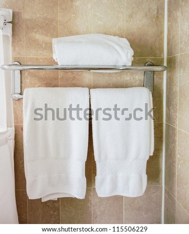 Clean white towel on Rack. Hotel amenities.