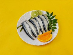 Cleaned and ready to cook fresh Indian oil sardine (Sardinella longiceps) on a Plate with curry leaves ,orange slice and lemon slice. Isolated on Yellow Background.