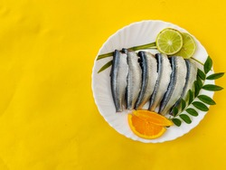Cleaned and ready to cook fresh Indian oil sardine (Sardinella longiceps) on a Plate with curry leaves ,orange slice and lemon slice. Isolated on Yellow Background.Space for text.