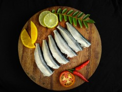 Cleaned and ready to cook fresh Indian oil sardine (Sardinella longiceps) on a wooden pad with curry leaves ,orange slice and lemon slice.