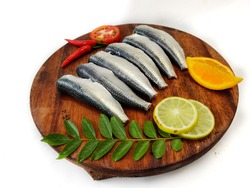Cleaned and ready to cook fresh Indian oil sardine (Sardinella longiceps) on a wooden pad with curry leaves ,orange slice and lemon slice. Isolated on White Background.