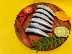 Cleaned and ready to cook fresh Indian oil sardine (Sardinella longiceps) on a wooden pad   with curry leaves ,orange slice and lemon slice. Isolated on Yellow Background.