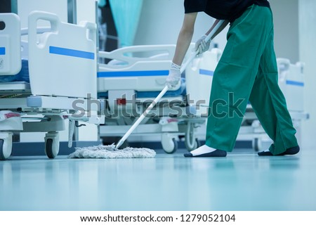 Cleaner,hospital cleaning,cleaner with mop and uniform cleaning hall floor,cleaning floor with mop in patient room,Cleaning the hospital floor