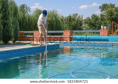 Cleaner swimming pool. Man cleaning outdoor swimming pool with vacuum tube cleaner in summer. Seasonal preparations. Cleaning systems for swimming pools. Dirty outdoor pool