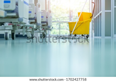 Cleaner using mops, cleaner with mop and uniform cleaning hall floor, hospital cleaning floor with mop in patient room the hospital epoxy floor.