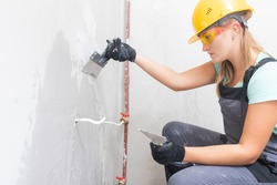 Cleaning a concrete wall from defects, repair and construction, surface preparation with spatula before applying plaster.