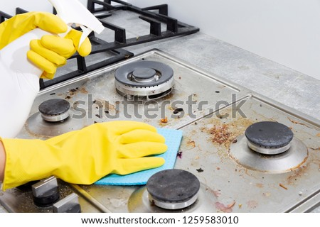 Cleaning a gas stove with kitchen utensils, household concepts, or hygiene and cleaning. Сток-фото ©