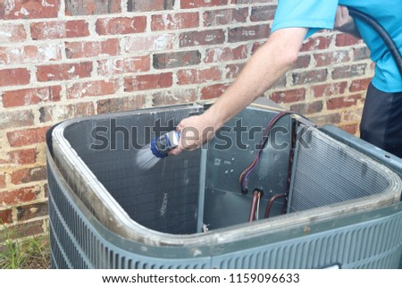 Cleaning Air Conditioner Condenser Coil - Shutterstock ID 1159096633