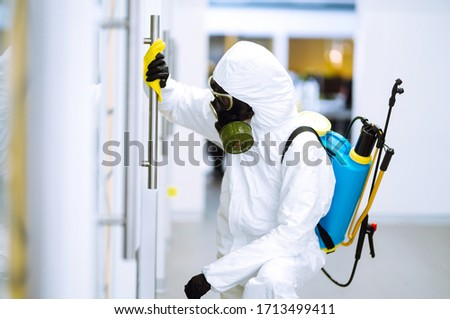 Cleaning and disinfection of office to prevent COVID-19, Man in protective hazmat suit washes office furniture to preventing the spread of coronavirus, pandemic in quarantine city.