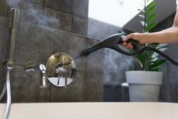 Cleaning and disinfection of the bathroom tap with steam. Professional cleaning process