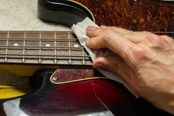 Cleaning and polishing electric bass guitar with microfiber cloth