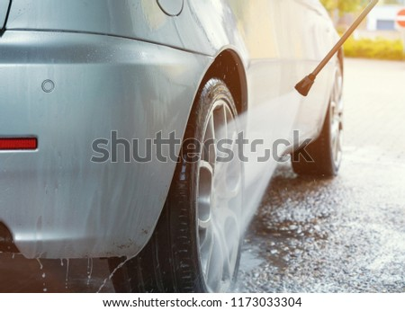 Cleaning beatiful rims of an italian car at car wash park with steam radiator #1173033304