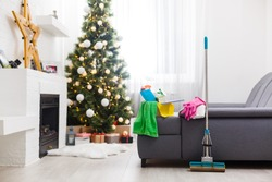 Cleaning before Christmas. Multicolored cleaning supplies. Sponges, rags and spray with festive decorations against modern home background