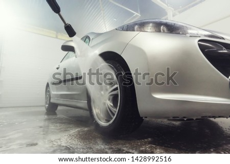 Cleaning Car Using High Pressure Water. Man washing his car under high pressure water in service. Self-cleaning stylish car in the garage. Wash kolesnogo drive. #1428992516