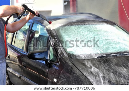 Cleaning Car Using High Pressure Water. Man washing his car under high pressure water in service #787910086