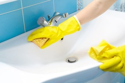 Cleaning - cleaning bathroom sink and faucet with detergent in yellow rubber gloves with orange sponge - housework, spring cleaning concept