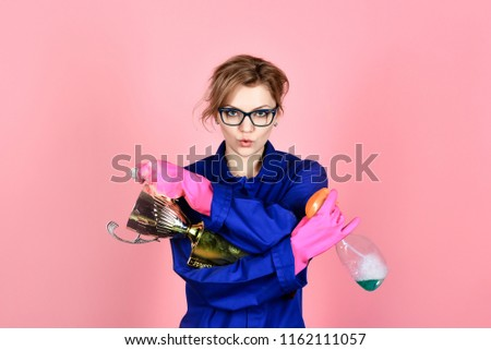 Cleaning, cleanliness, cleaning products, housework, housekeeping. Woman in uniform and gloves holds cleanser spray and gold trophy cup. Woman from professional cleaning service. Duties, domestic work