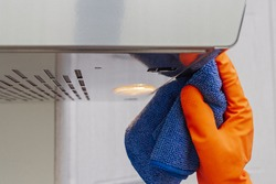 Cleaning domestic cooker hood. Women's hands clean the kitchen hood with a cloth