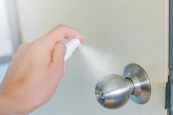 Cleaning door knob,Spraying alcohol on the doorknob. Before opening the door with alcohol spray for Coronavirus prevention ,Hand sanitizer