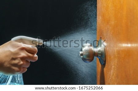 Cleaning door knob with alcohol spray for  Covid-19 (Coronavirus) prevention. Foto stock ©