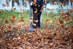 Cleaning dry leaves with a wind turbine. The gardener is cleaning the garden. Autumn cleaning of the yard.