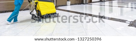 Cleaning floor with washing machine in office lobby or school. Panoramic view of corporate interior during cleaning with vacuum equipment. Clean shiny marble floor. Concept of commercial service.