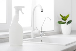 Cleaning fluid bottle on kitchen window and white sink background