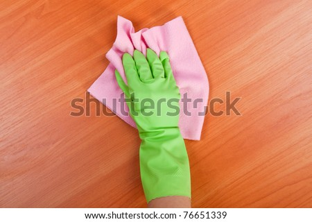 Cleaning furniture table in green glove with pink sponge