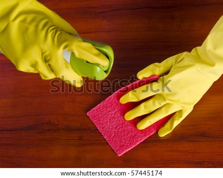 Cleaning furniture table in yellow gloves with red sponge