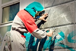 Cleaning graffiti from a building wall