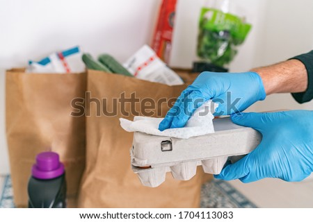 Cleaning groceries man at home wiping egg package with sanitizing wipes at home after shopping or receiving online delivery grocery store bags.
